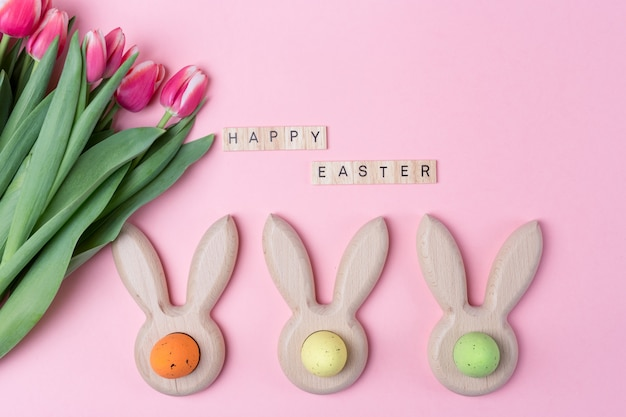 Easter holiday pink background with colored eggs in bunny ears. happy easter wooden letters. flat lay.
