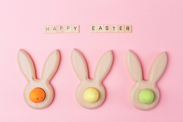 Easter holiday pink background with colored eggs in bunny ears shaped egg cups. happy easter wooden letters. flat lay.