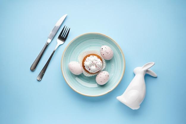 Сервировка стола к пасхальному празднику и тарелки с разноцветными яйцами на синем