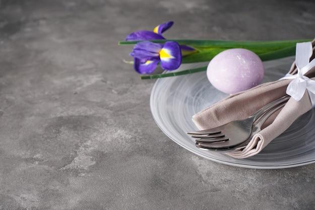 Сервировка стола к пасхальному празднику и тарелки с разноцветными яйцами на сером