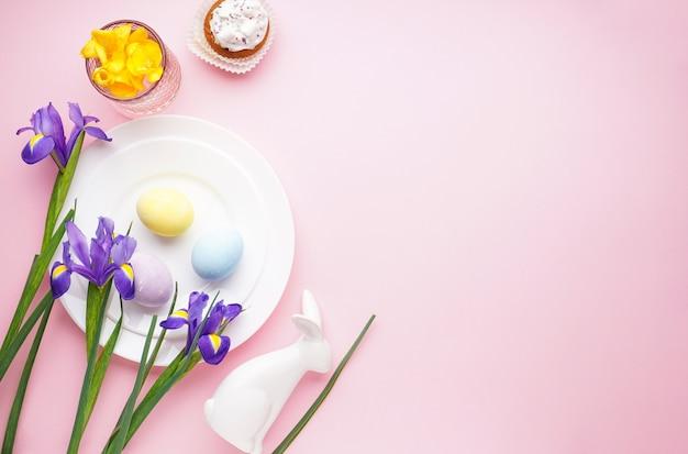 Сервировка стола к пасхальному празднику и тарелки с разноцветными яйцами на розовом
