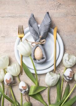 白いプレートとチューリップの花に卵からのバニーとイースターの休日のテーブルの設定。