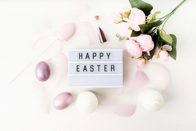 Пасха. световой короб счастливой пасхи, вид сверху, украшенный яйцами пастельных тонов и перьями