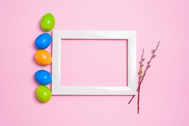 Easter holiday willow branches and colorful painted eggs photo frame on a pastel pink background