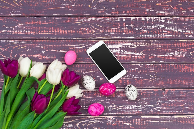 Easter, holidays, tradition and object ,close up of colored easter eggs, tulip flowers and smartphone