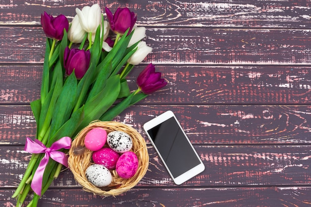 Easter, holidays, tradition and object concept - close up of colored easter eggs, tulip flowers and smartphone on wooden background