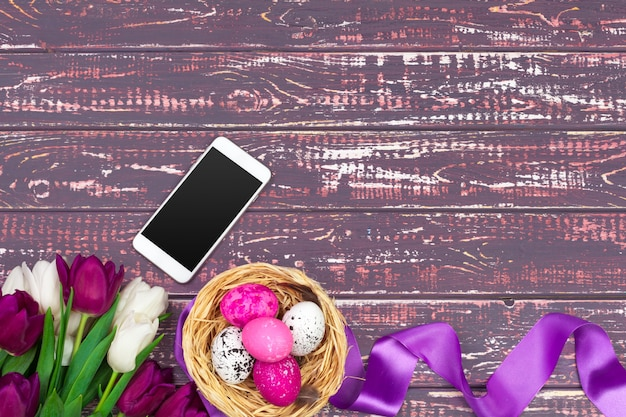 Easter, holidays, tradition and object concept - close up of colored easter eggs, tulip flowers and smartphone