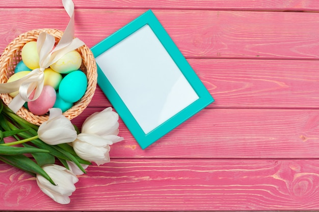 Easter, holidays, tradition and object concept - close up of colored eggs and tulip flowers over wooden boards
