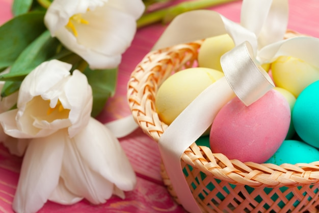 Easter, holidays, tradition and object concept - close up of colored eggs and tulip flowers
