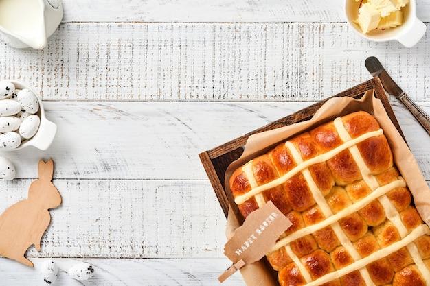 Пасхальные булочки с горячим крестом. традиционный завтрак и пасхальная выпечка праздничных украшений кролика на белом деревянном