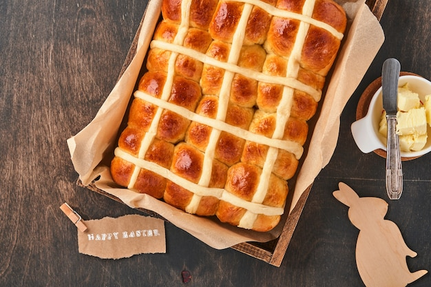 Пасхальные булочки с горячим крестом. традиционный завтрак и пасха выпечки праздничные украшения rabbiton темный старый деревянный фон. яркие цвета, вид сверху на деревянный стол.