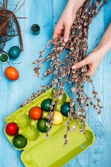 青い木製のテーブルの上のオフィスの職場でイースター。女性の手と柳の枝