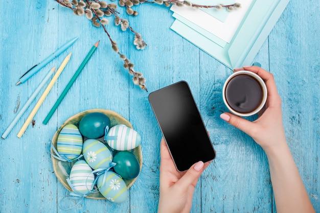 青い木製のテーブルの上のオフィスの職場でイースター。電話と一杯のコーヒーと女性の手