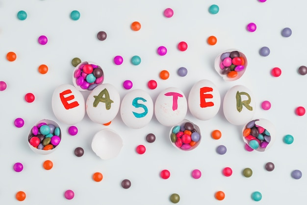 Easter inscription on eggs with candies on table