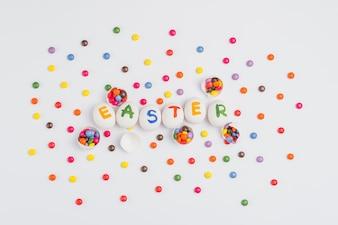 Пасхальная надпись на яйцах с конфетами на светлом столе