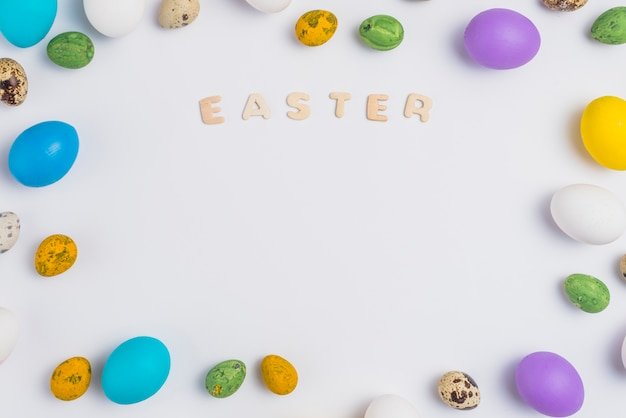 Easter inscription with colorful eggs on table