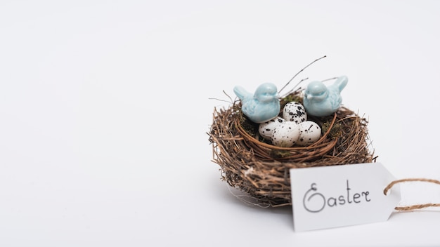Easter inscription with quail eggs in nest on table