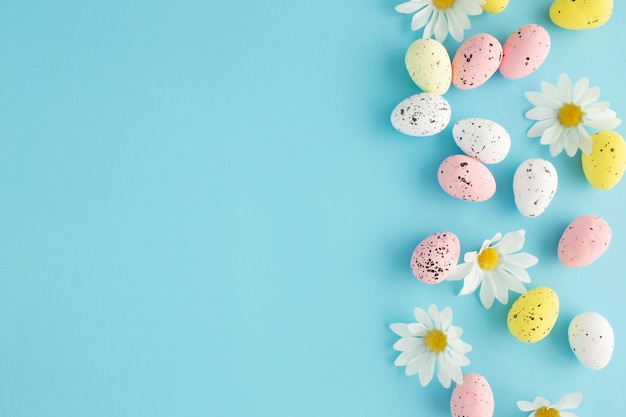 コピースペースと青い背景に卵とデイジーとイースターの招待状