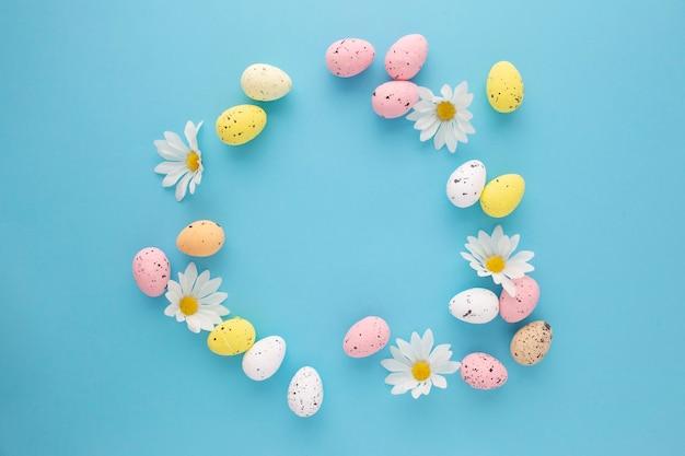 Invito di pasqua con uova e margherite su sfondo blu con spazio di copia