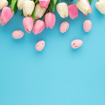 Easter invitation with tulips on a blue background with copy space