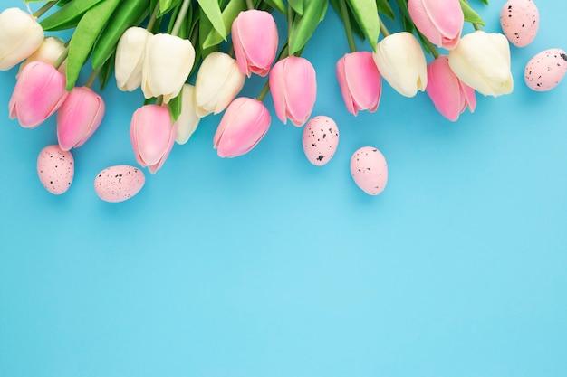 Invito di pasqua con i tulipani su sfondo blu con spazio di copia