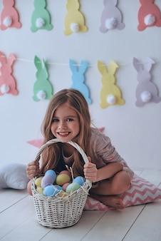 부활절은 그녀가 가장 좋아하는 휴일입니다. 부활절 바구니를 들고 배경에 장식이 있는 베개에 앉아 웃고 있는 사랑스러운 소녀