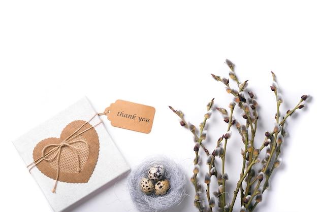 Пасха изолирована с перепелиными яйцами в гнезде с веткой ивы и подарочной коробкой с биркой спасибо