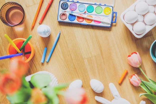 나무 테이블에 계란과 꽃 그림 도구와 부활절 라이프 스타일 배경. 위에서 봅니다.