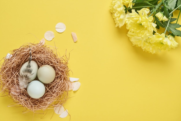 Easter light blue eggs in white vintage metal holder with feathers, ribbon, yellow chrysanthemums flowers and blank paper for text on yellow table.