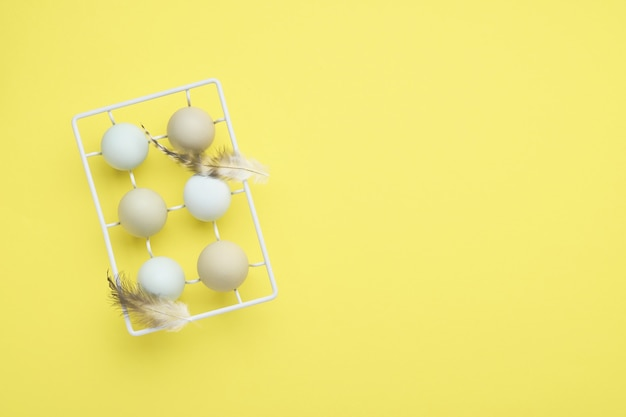 Easter light blue eggs in white vintage metal holder with feathers yellow on table. top view
