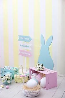 イースター!バニーと花のバスケットが付いている多くのイースターエッグ!イースタールームの装飾と装飾、子供用プレイルーム。カラフルな塗装イースターエッグとウサギ。春の家の装飾、春の花