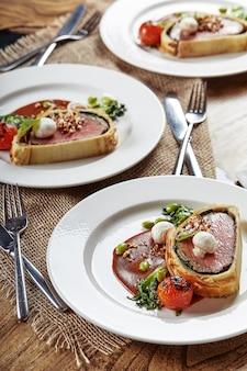 부활절 고기 롤, 부활절 저녁 식사를 위한 미트 로프. 다양한 음식 스낵과 에피타이저로 아름답게 장식된 케이터링 연회 테이블.