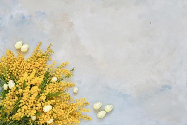 Пасхальный. цветы мимозы и пасхальное украшение на синем. копировать пространство