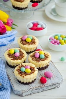 イースターミニブラウニーチーズケーキ鳥の巣とチョコレートとキャンディーの卵。イースターデザート。子供のための面白い食べ物のアイデア。垂直方向。セレクティブフォーカス。