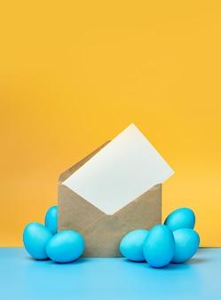 Пасхальный макет. сделайте конверт с листом бумаги и пасхальными яйцами на желтом фоне с копией пространства.