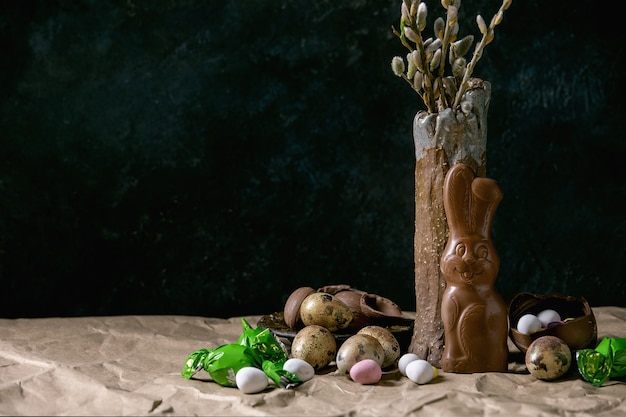 세라믹 꽃병에 꽃 버드 나무 가지, 전통적인 초콜릿 토끼, 계란 및 구겨진 공예 종이가있는 테이블에 과자가있는 부활절 분위기 정물.