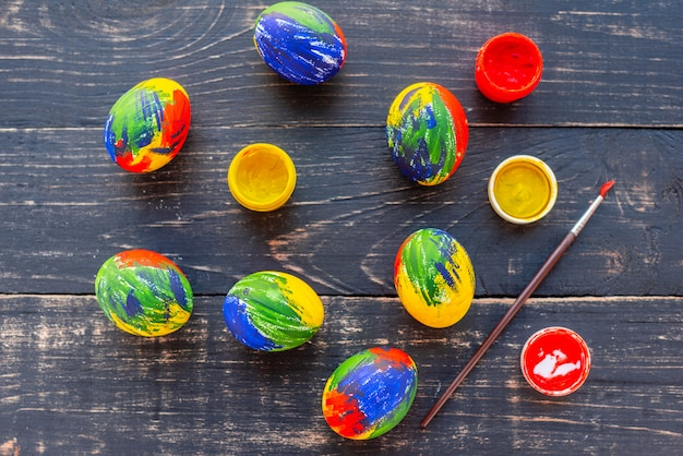 Easter multi-colored eggs, paints and brush on a table. preparation for a holiday