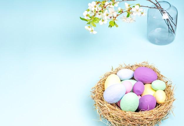 青い背景の花瓶に咲く桜の枝を持つイースターマルチカラー卵。季節性のコンセプト、春、はがき、休日。フラットレイ、コピースペース、テキスト用のスペース。閉じる。
