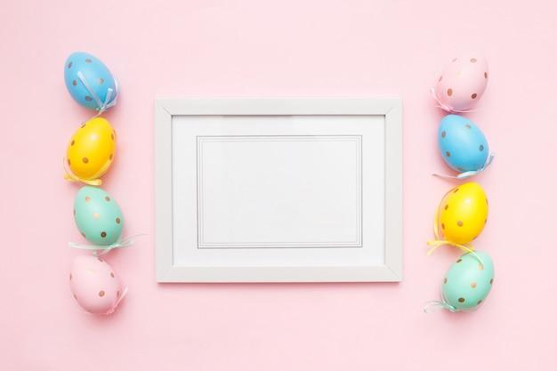 Пасхальные разноцветные яйца и белая фоторамка на розовом