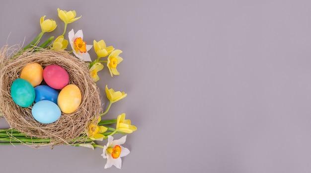 Разноцветные пасхальные яйца с букетом желтых тюльпанов и нарциссов на сером фоне, с копией пространства