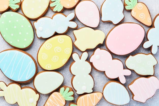 Пасхальные разноцветные имбирные пряники, конфеты и разбросанные кондитерские изделия, украшающие заправку на сером столе. стол для выпечки пасхи. концепция праздничного стола. место для текста.
