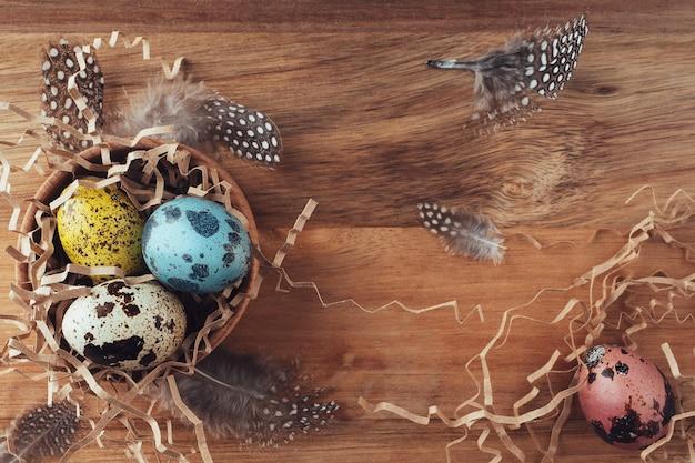 干し草で作られたイースターの巣。木製の背景に色付きの卵と羽が描かれています。フラットフラット、上面図、コピースペース。イースターの背景。伝統的なレトロなスタイルのイースターのコンセプト。