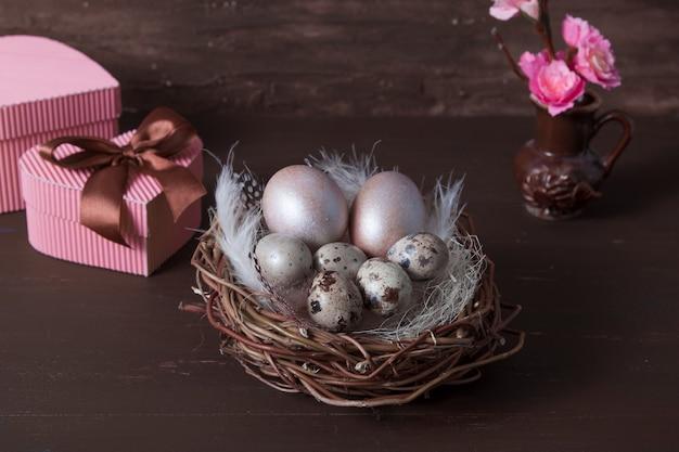 Пасхальное гнездо с яйцами на коричневом фоне с розовыми цветами и подарочными коробками