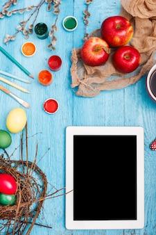 Pasqua sul posto di lavoro d'ufficio sulla tavola di legno blu. laptop e una tazza di caffè