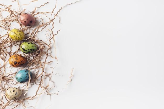 イースターは、白い背景、フラットフラット、上面図、コピースペースに卵と干し草を描いた。ミニマルなイースターの背景。ハッピーイースターのご挨拶。