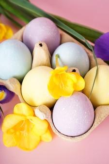Пасхальные крашеные яйца в подносе для яиц с цветами на желтом фоне. крупный план