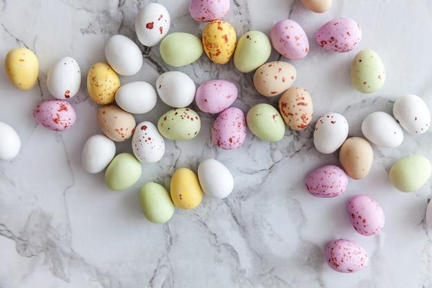 トレンディな灰色の大理石の背景にイースターパステルキャンディチョコレート卵のお菓子