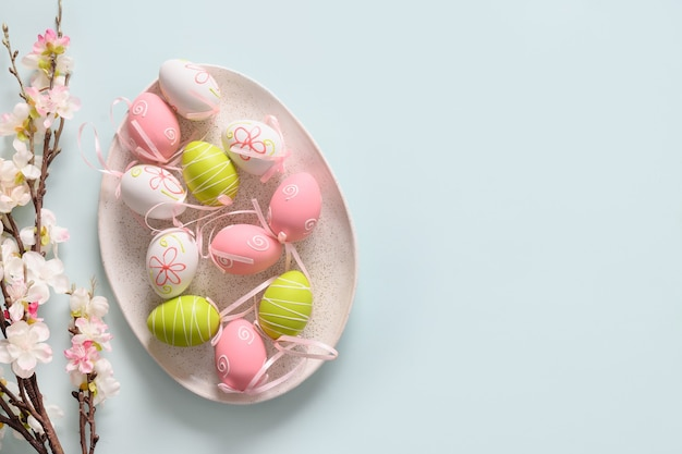 Easter pastel eggs in plate and spring blooming flowers on blue. view from above. space for text.