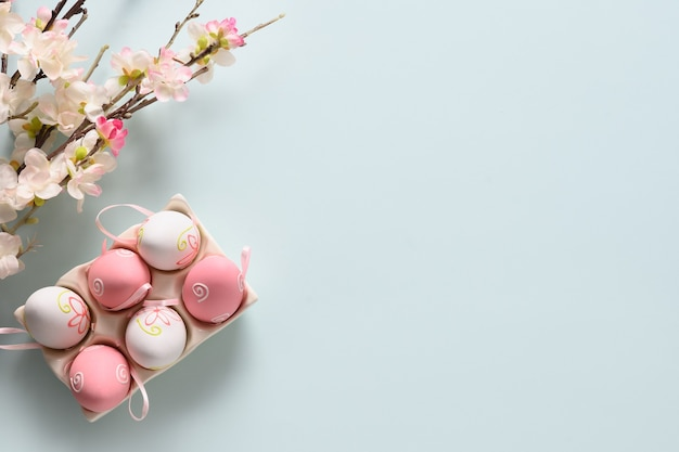 Easter pastel eggs and spring blooming flowers on blue.