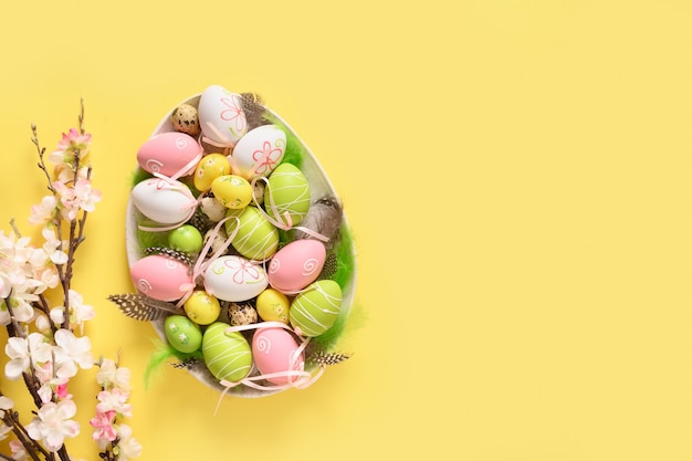 Easter pastel eggs and spring blooming flowers